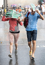 © Licensed to London News Pictures. 27/07/2018. London, UK. People try to run for cover as they get caught in a sudden downpour near Parliament as heavy rain ends the long dry spell. Photo credit: Peter Macdiarmid/LNP