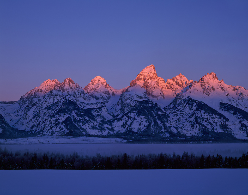 """The Teton Range at sunrise is a mountain range of the Rocky Mountains in North America. A north-south range, it is on the Wyoming side of the state's border with Idaho, just south of Yellowstone National Park. Most of the range is in Grand Teton National Park.<br /> <br /> Early French Voyageurs used the name """"les Trois Tétons"""" (the three breasts).[1] It is likely that the Shoshone people once called the whole range Teewinot, meaning """"many pinnacles"""".[2]<br /> <br /> The principal summits of the central massif, sometimes referred to as the Cathedral Group, are Grand Teton (13,770 feet (4,200 m)), Mount Owen (12,928 feet (3,940 m)), Teewinot (12,325 feet (3,757 m)), Middle Teton (12,804 feet (3,903 m)) and South Teton (12,514 feet (3,814 m)). Other peaks in the range include Mount Moran (12,605 feet (3,842 m)), Mount Wister (11,490 feet (3,500 m)), Buck Mountain (11,938 feet (3,639 m)) and Static Peak (11,303 feet (3,445 m))."""