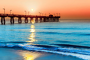 Fine Art: Seascape of the Pompano Pier and the Atlantic Ocean early morning during surise. Light surf, blue water and an orange sky on the ocean.