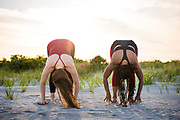 Two adult Woman, one caucasian, one black, performing yoga on a Rhode Island beach at dusk.