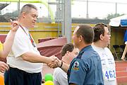Proud athlete shakes hands with policeman at award ceremony. Special Olympics U of M Bierman Field. Minneapolis Minnesota USA