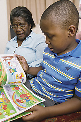 Grandmother listening to her grandson reading a book at home,
