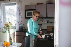 Senior woman taking cup of coffee from kitchen counter