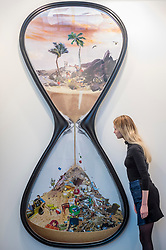 "© Licensed to London News Pictures. 15/01/2019. LONDON, UK. A staff member views ""Trickle"", 2018, by David Mach, at the Jill George Gallery stand.  Preview of London Art Fair 2019 at the Business Design Centre in Islington.  The annual fair showcases exceptional modern and contemporary art from the 20th century to present day and opens 16 to 20 January.  Photo credit: Stephen Chung/LNP"