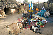 The Mustapha family in their courtyard in Dar es Salaam village, Chad, with a week's worth of food. Gathered around Mustapha Abdallah Ishakh, 46 (turban), and Khadidja Baradine, 42 (orange scarf), are Abdel Kerim, 14, Amna, 12 (standing), Nafissa, 6, and Halima, 18 months. Lying on a rug are (left to right) Fatna, 3, granddaughter Amna Ishakh (standing in for Abdallah, 9, who is herding), and Rawda, 5. From the book Hungry Planet: What the World Eats (Model Released)