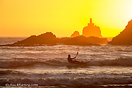 Surfing the waves at sunset on a kayak with Tilamook Rock Lighthouse at Ecola State Park near Cannon Beach, Oregon, USA