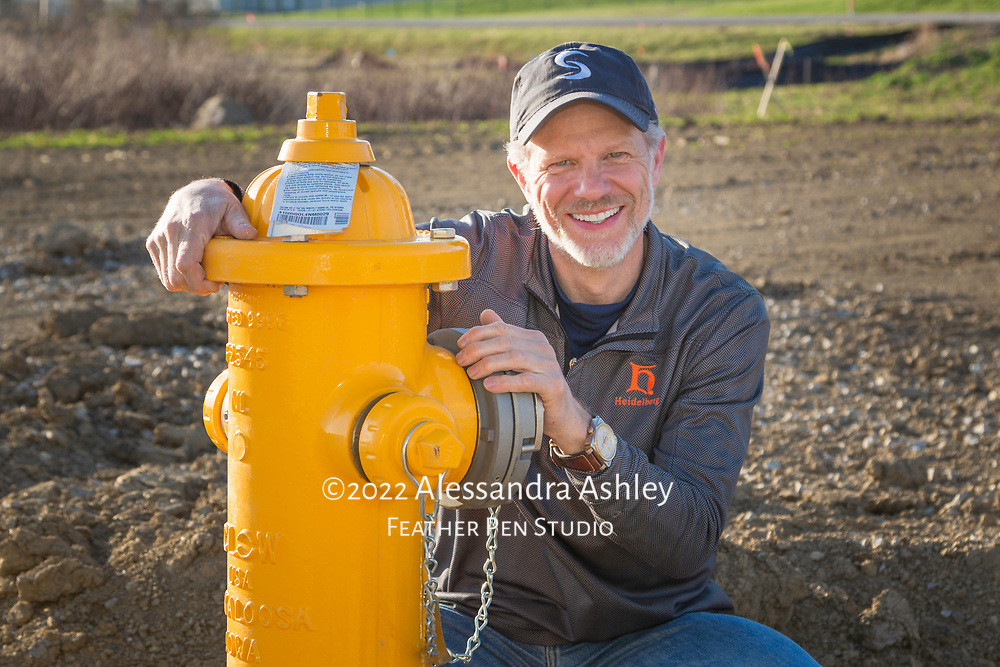 Business owner models newly installed fire hydrant at building site of new physical therapy and wellness center building.