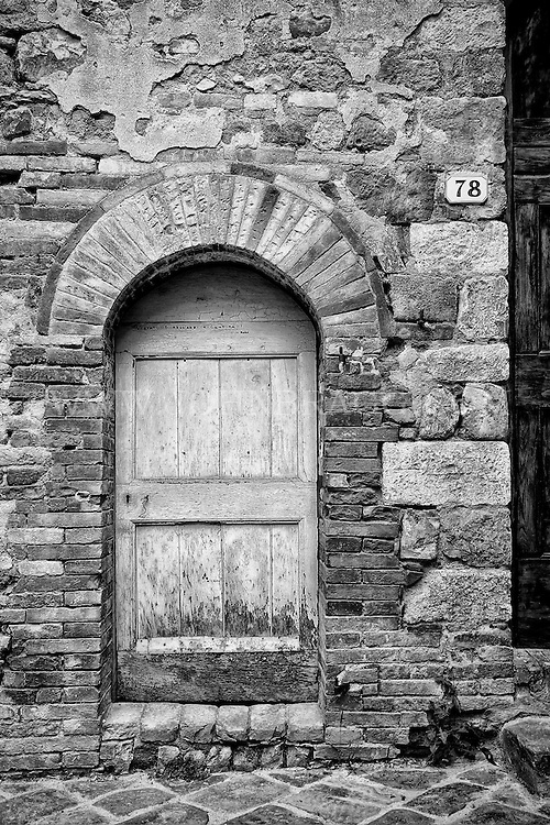 Black and white photo of a rustic, rounded door surrounded by stone along the streets of San Quirico d'Orcia, Italy.