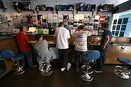Music enthusiasts listening to vinyl records on turntables at 3beat Records in Liverpool. The retailer specialised in dance music vinyl sales and was one of the dwindling number of independent record retailers in the United Kingdom. Although in long-term decline due to the popularity of compact discs, vinyl remained popular with collectors and DJs alike.