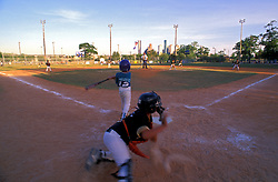 Stock photo of a catcher throwing a ball from home plate at a little league baseball game