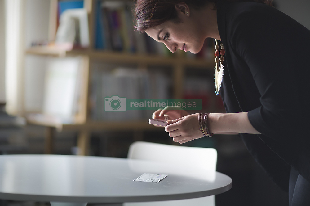 May 7, 2014 - Young woman depositing cheque with smartphone (Credit Image: © Image Source/ZUMAPRESS.com)
