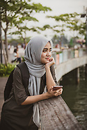 Aznih, age 23, with her smartphone at the waterfront in Kota Kinabalu, Sabah, Malaysia. (August 9, 2019)