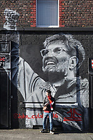 Football - 2019 / 2020 UEFA Champions League - Round of Sixteen, Second Leg: Liverpool (0) vs. Atletico Madrid (1)<br /> <br /> A fan sits in front of a Jurgen Kloop mural, at Anfield.<br /> <br /> <br /> COLORSPORT/TERRY DONNELLY