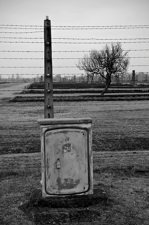 An electric box infront of an electric fence.