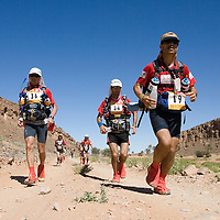 27 March 2007:  #36 Vincent Marescq of France (left), #34 Bruno Cuvillier of France (middle) and #19 Abdellatif Jalal of Morocco (right) run across the gorge of El Maharch during third stage of the 22nd Marathon des Sables between jebel El Oftal and jebel Zireg (20.07 miles). The Marathon des Sables is a 6 days and 151 miles endurance race with food self sufficiency across the Sahara Desert in Morocco. Each participant must carry his, or her, own backpack containing food, sleeping gear and other material.