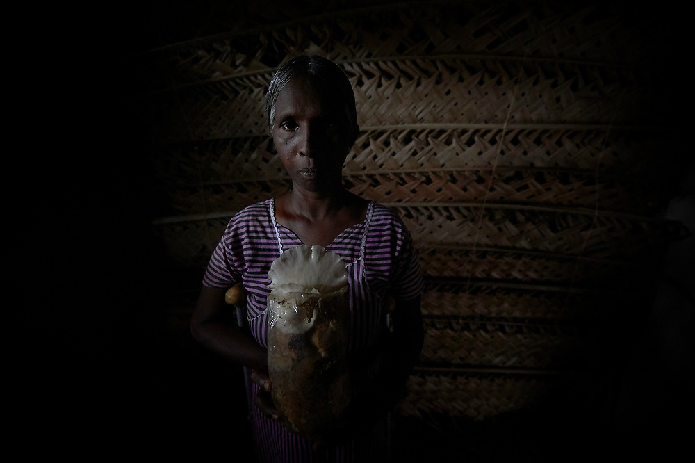 Thvarasa Thruamalar raises mushrooms in a dark room of her home in Parantan, Kilinochchi, Sri Lanka. She participates in a church-sponsored women's group, many of whose members are widows, their husbands killed during the country's brutal civil war. The group loaned her money to expand her mushroom business, which produces badly needed income for her family.