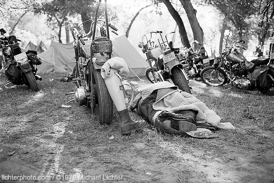 Early Morning. City Park, Sturgis, SD. 1979<br /> <br /> Limited Edition Print from an edition of 50. Photo ©1979 Michael Lichter.<br /> <br /> The Story: I arrived in Sturgis for my first bike week too late to see the lay of the land but just in time for the all night party that happened every night in City Park.  This then was my first morning in Sturgis.  I woke up not having slept much and assessed the damages, both internally and externally.  What sort of toll did the party take?  There was drag racing down the narrow pavement between the tents, there were campfires, wildness until all hours of the morning and a dreamlike recollection of police cars with lights flashing, screaming through the park in the middle of the night.