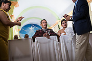 Rosalino and his wife, Sabina, wait to have a lasso placed on their shoulders by their sponsors during the couple's wedding ceremony. The lasso is a staple of Hispanic weddings and represents the couple's everlasting union. The two were officially married five years prior in a civil union, but it wasn't until March that they could afford to throw a proper celebration after they saved enough of the money that Rosalino earned as a migrant worker in the tobacco fields of Kentucky. Nick Wagner / Alexia Foundation