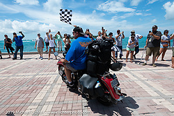 Curtis Venable riding over the finish line on his 1940 Harley-Davidson ULH Flathead at the end of the Cross Country Chase motorcycle endurance run from Sault Sainte Marie, MI to Key West, FL. (for vintage bikes from 1930-1948). The Grand Finish in Key West's Mallory Square after the 110 mile Stage-10 ride from Miami to Key West, FL and after covering 2,368 miles of the Cross Country Chase. Sunday, September 15, 2019. Photography ©2019 Michael Lichter.