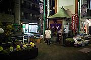 JAPAN, TOKYO, FEBRUARY 2013 -  A woman pray in front of a Small Shrine near a vegetable shop in Oimachi [FR] Une femme prie devant un petit temple shintoiste proche d'un marchand de legume a Oimachi