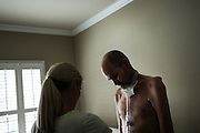 VESTAVIA HILLS, AL – DECEMBER 4, 2014: <br /> Former NFL fullback Kevin Turner (right) receives help changing his shirt from nurse Allison Sanford (right). Since his diagnosis with ALS in 2010, Turner's condition has deteriorated rapidly – leaving him dependent on a feeding tube for meals and a ventilator to help him breathe. Turner is one of the lead plaintiffs in the ongoing concussion litigation against the NFL. (Photo by Bob Miller/For The Washington Post)