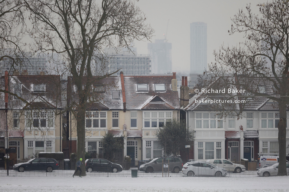 A jogger runs through snow, passing Edwardian period homes bordering Ruskin Park, south London during the bad weather covering every part of the UK and known as the 'Beast from the East' because Siberian winds and very low temperatures have blown across western Europe from Russia, on 1st March 2018, in Lambeth, London, England