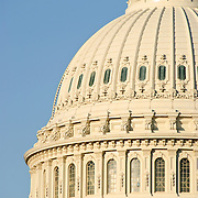 Dome of the US Capitol Building of the US Congress with side lighting showing the detail and a clear blue sky. This is the front of the building, with the statue on top facing forward.