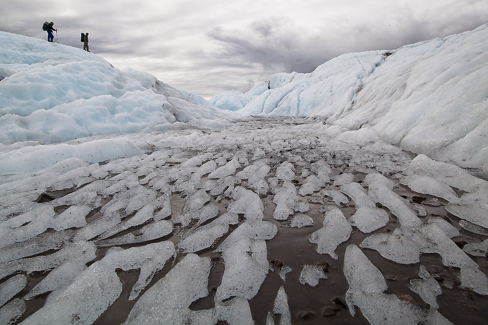 Parmenter and Liana Welty explore the dynamic surface of the Root Glacier, Wrangell-St. Elias National Park, Alaska. Melt channels form on the surface along which sediment is deposited, forming abstract black and white patters in the ice.