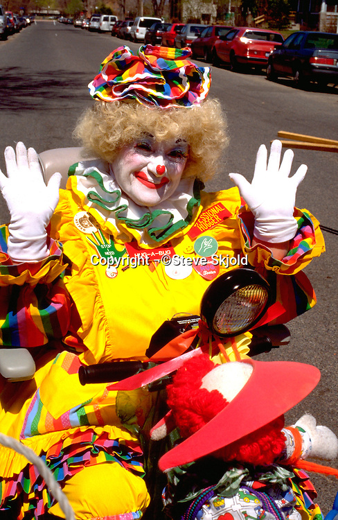 Clown woman in wheelchair age 55 at In the Heart of the Beast May Day Festival and Parade.  Minneapolis  Minnesota USA