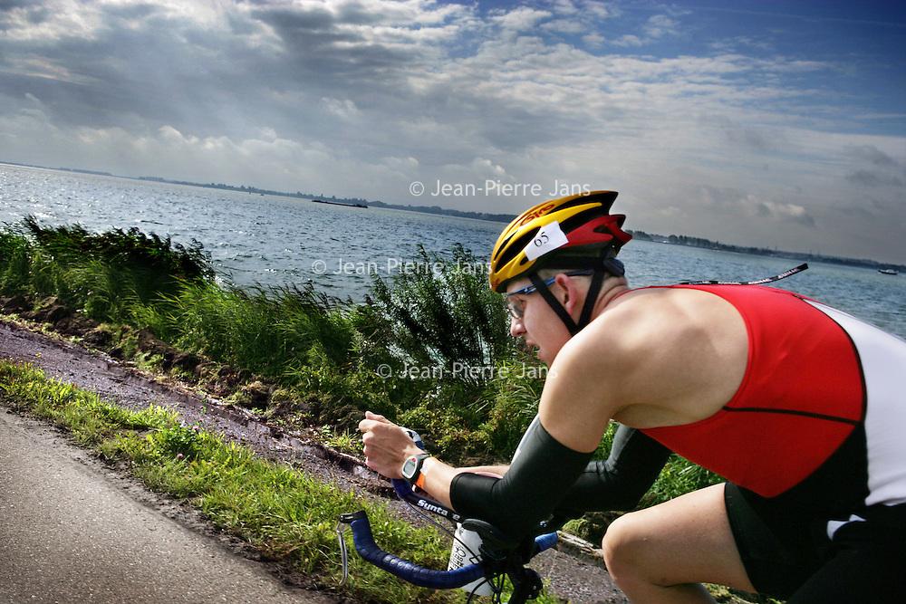 Nederland.Almere Haven.27 augustus 2005.<br /> Een van de tri-atleten fietsend langs het IJsselmeer tijdens de 40 km wielrennen, het 2e onderdeel van de Holland Triathlon. Sport.Wielrennen.Doorzettingsvermogen.Wielerhelm.Hollandse luchten.Water.Dynamiek.Sportief.Atletiek.<br /> Participants in the Holland Triathlon 2005.