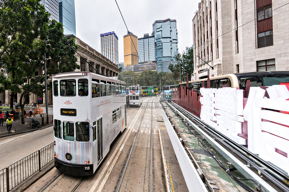 Historic double decker trams passes Statue Square in the central district of Hong Kong.