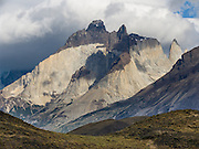 """Los Cuernos soar above Torres del Paine National Park, Chile, South America. """"The Horns"""" (about 2100 meters elevation) are a pinkish-white granodiorite intrusion formed 12 million years ago topped with an older crumbly dark sedimentary rock, exposed by freeze-thaw erosion and glaciation. The foot of South America is known as Patagonia, a name derived from coastal giants, Patagão or Patagoni, who were reported by Magellan's 1520s voyage circumnavigating the world and were actually Tehuelche native people who averaged 25 cm (or 10 inches) taller than the Spaniards."""