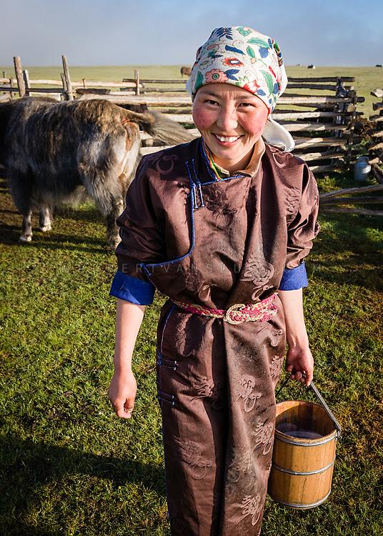 A farm girl carries a vat of fresh yak milk in the grasslands of Khovsgol Province, Mongolia. Photo © Robert van Sluis