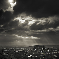Sun breaking over Edinburgh castle from Arthurs seat