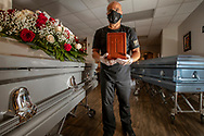 The onset of the coronavirus pandemic means Vior Funeral Home is busier now than ever before. According to Jorge Rivero, the funeral home's owner and director, his business is dealing with one COVID-19 case per day -- that's in addition to deaths caused by other illnesses, of which he's also noticed an uptick. Until now, every single COVID-19 case the Vior Funeral Home has dealt with has been cremated, though families can also choose to bury their loved ones in body bags. Because cemeteries are limiting their hours of operation due to the pandemic, the funeral home has to hold on to bodies longer, with several caskets currently lining the facility's lobby. Rivero is photographed next to some of these caskets on Tuesday, April 21, 2020. He's holding an urn similar to the ones used to hold the remains of coronavirus patients.