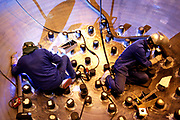 Workers weld the adaptators of the top of a tank in Areva Saint-Marcel plant, in Chalon sur Saone, France, on July 29, 2005. Photo by Lucas Schifres/Pictobank