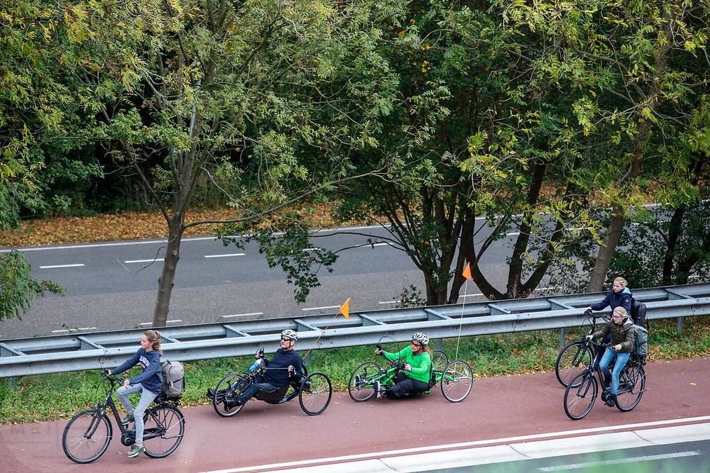 Handbikers rijden tussen fietsende scholieren in Nijmegen.<br /> <br /> Hand bikers ride between cyclists in Nijmegen.
