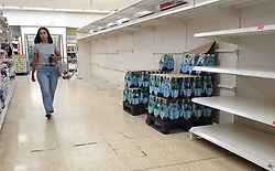 © Licensed to London News Pictures. 31/07/2021. London, UK. A shopper walks past nearly-empty shelves of bottled drink water in Sainsbury's, north London. Record breaking numbers of people have been forced to self-isolate after being alerted by the NHS Covid-19 app. The pingdemic has seen staff shortages at supermarkets, resulting in less stock making its way to supermarket shelves. Labour leader Sir Keir Starmer has demanded that the government brings forward the end to self-isolation from 16 August to 7 August. Photo credit: Dinendra Haria/LNP