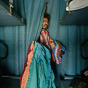 Peddler selling Cushion covers. Throughout the journey, peddlers pop into the train compartments with all sorts of offerings,  to be bargained for a few rupees.<br /> Inside the Dibrugarh-Kanyakumari Vivek Express, the longest train route in the Indian Subcontinent. It joins Kanyakumari, Tamil Nadu, which is the southernmost tip of mainland India to Dibrugarh in Assam province, near the border with Burma.