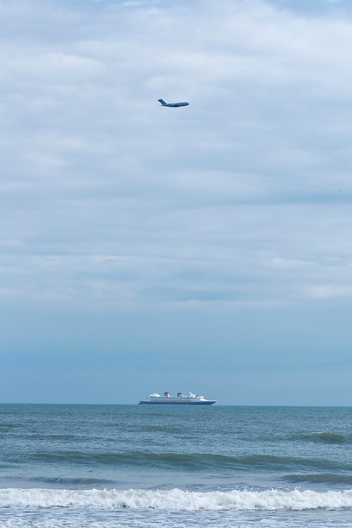 Cocoa Beach, Florida - December 14, 2020: A U.S. Air Force Boeing C-17 Globemaster III flies over a Disney cruise ship as it descends for landing at Patrick Air Force Base.