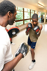Teenage boy and boxing trainer in boxing summer class Haringey London UK