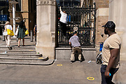 A woman climbs down from the railings at one of the entrances to Liverpool Street mainline station in the City of London, the capital's financial district, on 8th June 2021, in London, England.