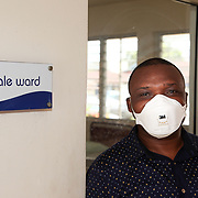 INDIVIDUAL(S) PHOTOGRAPHED: Ibiam Azu Agwu. LOCATION: Tuberculosis Hospital, Calabar, Cross River, Nigeria. CAPTION: Ibiam Azu Agwu, who manages the HFG Project in Cross River, prepares to enter the isolation room where patients diagnosed with tuberculosis stay. Masks are a basic precaution against the spread of tuberculosis.