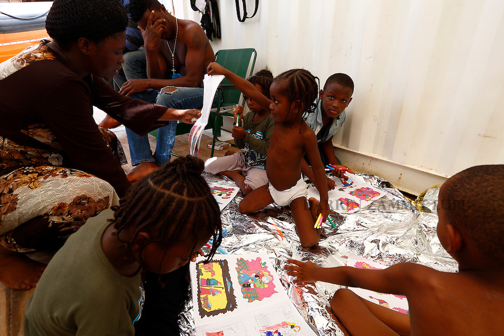Migrant children use colouring books on the deck of the Medecins san Frontiere (MSF) rescue ship Bourbon Argos somewhere between Libya and Sicily August 8, 2015.  Some 241 mostly West African migrants on the ship are expected to arrive on the Italian island of Sicily on Sunday morning, according to MSF.<br /> REUTERS/Darrin Zammit Lupi <br /> MALTA OUT. NO COMMERCIAL OR EDITORIAL SALES IN MALTA