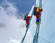 Climbers ascend ladders across large crevasses in Khumbu icefall, during climb of Chomolungma, Mt Everest, Nepal, Himalaya