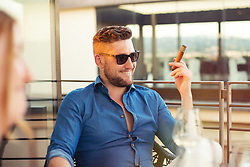 Man smoking cigar at rooftop bar, Florence, Italy. 27/08/15. Photo by Andrew Tallon