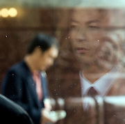 An attendant is reflected in a window of the Great Hall of the People during a session of the National People's Congress after a session in the Great Hall of the People. Chinese leaders are trying to improve energy efficiency to reduce both environmental damage and China's reliance on imported oil, which they see as a strategic weakness.