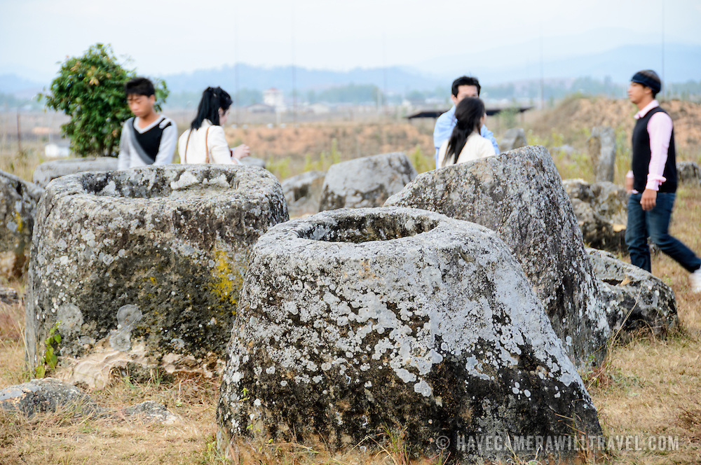 Visitors amongst the stone jars at Site 1 of the Plain of Jars in north-central Laos. Much remains unknown about the age and purpose of the thousands of stone jars clustered in the region. Most accounts date them to at least a couple of thousand years ago and theories have been put forward that they were used in burial rituals.