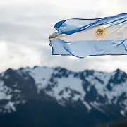 The flag of Argentina flies in a strong breeze against the snow-covered mountains near Ushuaia, Argentina.