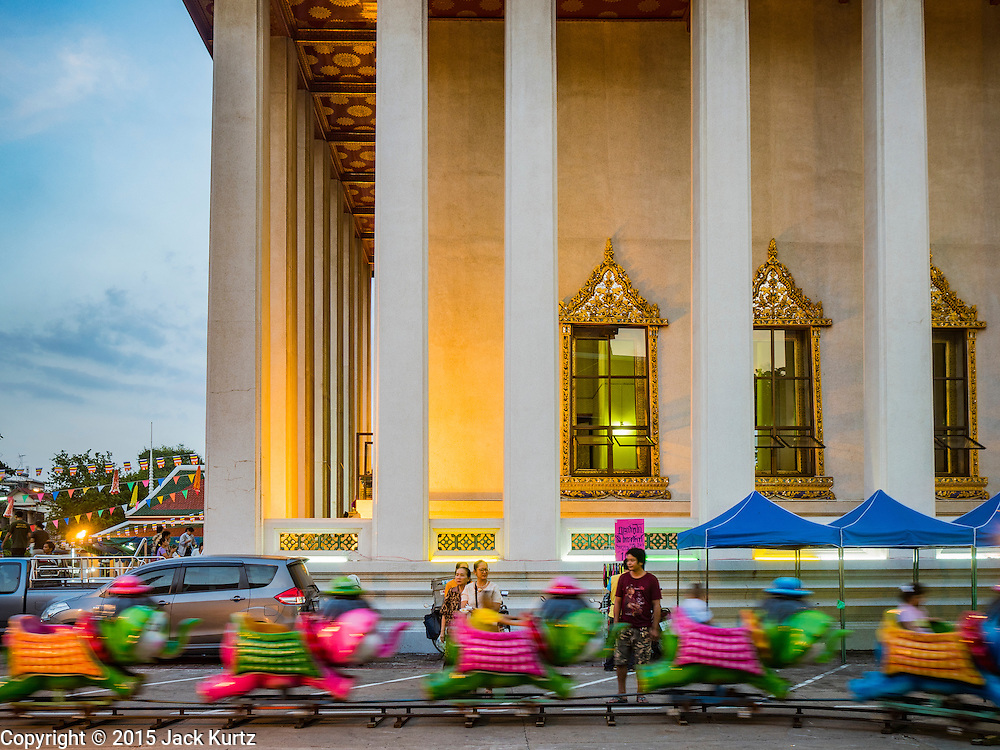 24 NOVEMBER 2015 - BANGKOK, THAILAND:  Children ride a train at the Wat Saket temple fair. Wat Saket is on a man-made hill in the historic section of Bangkok. The temple has golden spire that is 260 feet high which was the highest point in Bangkok for more than 100 years. The temple construction began in the 1800s in the reign of King Rama III and was completed in the reign of King Rama IV. The annual temple fair is held on the 12th lunar month, for nine days around the November full moon. During the fair a red cloth (reminiscent of a monk's robe) is placed around the Golden Mount while the temple grounds hosts Thai traditional theatre, food stalls and traditional shows.       PHOTO BY JACK KURTZ